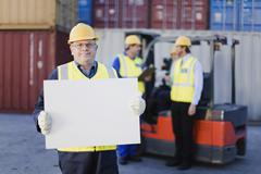 Worker holding sheet in shipping yard - stock photo