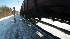 Freight train cars rushing on winter railway. Railroad in woods, Russia - stock footage