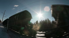 Sun shining through the driving freight cars of train at winter sunny day - stock footage