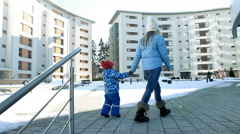 Mother and son go home at winter sunday Stock Footage