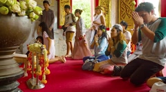 Buddhists kneel, pray and give offerings before an altar at Wat Chalong Stock Footage