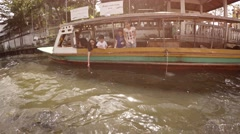 Tourists feeding fish from a passenger boat on the Chao Phraya river. Stock Footage