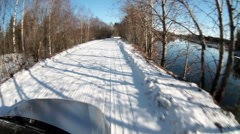 Car driving through the sunny winter forest at snowy bad road, front view Stock Footage