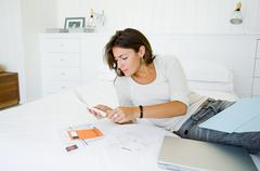 Woman on bed organising home finances Stock Photos