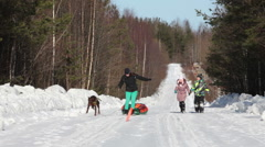 Caucasian mother with son and daughter walking at winter road with doberman dog - stock footage