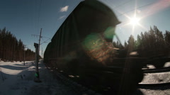 Freight cars of train driving by railway in winter sunny day, close-up. Loop - stock footage