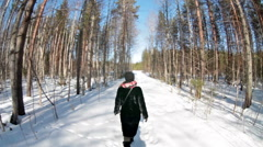 Camera follows young woman weared fur coat walking at winter forest, wide angle Stock Footage
