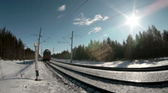 Freight train with locomative at the head passes on winter railroad in forest Stock Footage