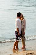 Young couple kissing on beach Stock Photos