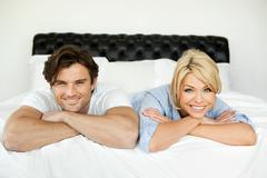 Couple lying on bed, portrait Stock Photos