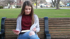Young girl reads and bookmarks her spot in book, video Stock Footage