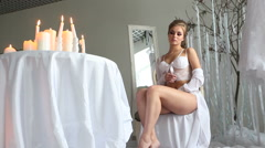 Sexy caucasian woman   in white negligee and white underwear with candles Stock Footage