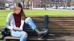 Tween girl relaxing on park bench and reading, video Stock Footage