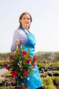 Woman holding hanging basket, portrait - stock photo