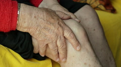 Closeup of an Old Woman Massaging Her Knee on the Couch Stock Footage