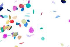 Close-up shot of decorative multi colored confetti falling against plain whit - stock photo
