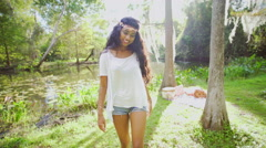 Stock Video Footage of Portrait of Asian Indian girl wearing denim shorts walking in park USA
