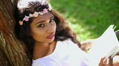 Portrait of pretty Indian Asian female enjoying sunshine in the park Stock Footage