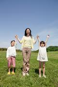 Mother with two children in field with arms up - stock photo