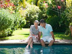 Couple sitting at poolside in garden Stock Photos