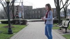 Tween girl texting on sidewalk, video - stock footage