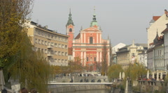 People relaxing by Ljubljanica River and others crossing a bridge in Ljubljana Stock Footage