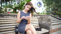 Young Hispanic female sitting outdoors texting on her smart phone Stock Footage