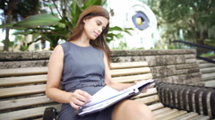Ambitious Latin Brazilian girl outdoors with her date planner Stock Footage