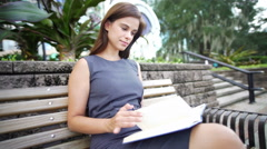 Young Hispanic American girl sitting outdoors with a diary Stock Footage