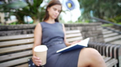Latin American female sitting outside downtown with her planner drinking coffee Stock Footage