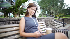 Young Hispanic female outdoors with coffee using earbuds with her smart phone Stock Footage