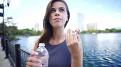 Pretty Latin American female outdoors enjoying some water and a cereal bar Stock Footage