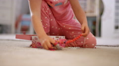 Little girl sitting in her room in her pajamas showing off her jewelry Stock Footage
