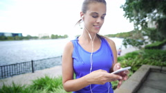 Healthy Brazilian girl in exercise clothing with her smart phone Stock Footage
