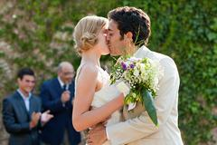 Newlyweds kissing at marriage ceremony Stock Photos