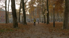 Man with yellow t-shirt walking in the park in Ljubljana Stock Footage