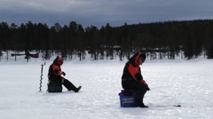 People do winter ice fishing at the lake in Trysil, Norway. Stock Footage