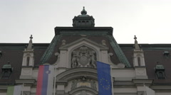 Flags slowly moving in front of the University building in Ljubljana Stock Footage