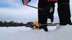 People drill hole in the ice for ice fishing at the lake in Trysil, Norway Stock Footage