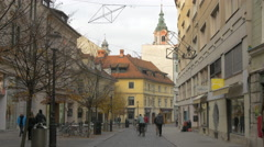 Young lady riding a bike and other people walking on a paved street in Ljubljana Stock Footage