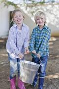 Children carrying heavy pail outdoors Stock Photos