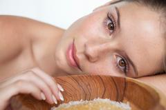 Woman laying by bowl of sugar Stock Photos