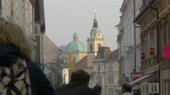 People riding bikes and walking close to the cathedral in Ljubljana Stock Footage