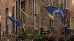 Three flags waving on a stone building in Edinburgh, UK Stock Footage
