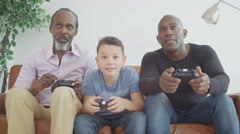 4K 3 Male generations of happy family playing video games together at home - stock footage