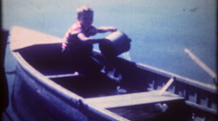 1107 young boy bailing water out of sinking boat - vintage film home movie Stock Footage