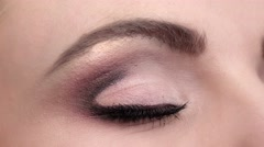 Beautiful woman eye blue eyes looking up. Closeup - stock footage
