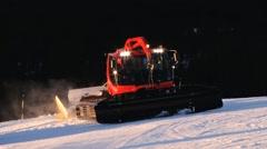 People drive snowcat machines preparing ski slopes at sunset in Trysil, Norway. Stock Footage