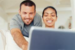 Couple using laptop in living room Stock Photos