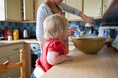 Toddler girl baking with mother - stock photo